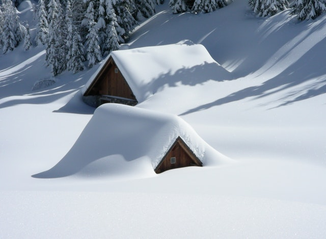 View of two cabin roofs barely showing under deep snow.