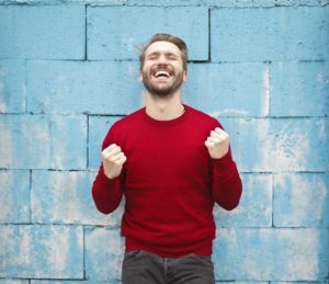 Happy man in red sweater in front of light blue block wall.